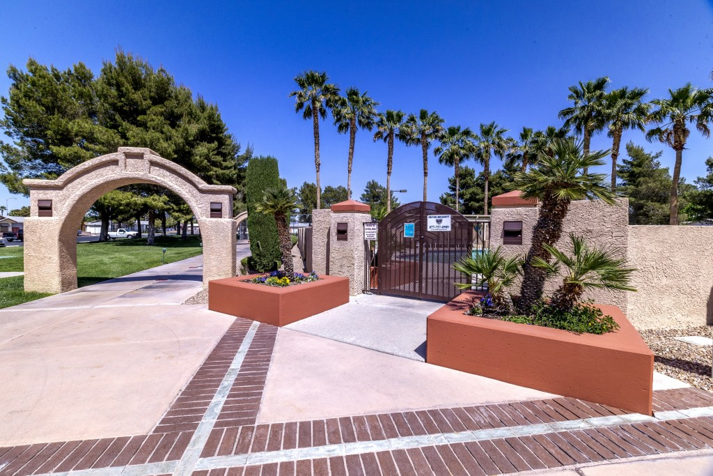 Gated entrance to pool area. Small palms planted at entrance. Large stone arch over paved walkway. Very tall palm trees in background.