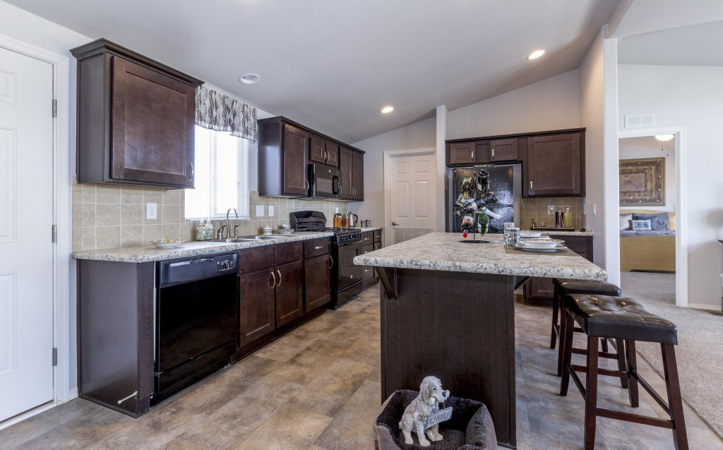 New kitchen with open floor plan. Vaulted ceilings with recessed lighting. Hardwood floors and dark wood cabinets. Long kitchen island with granite countertops. Black appliances.