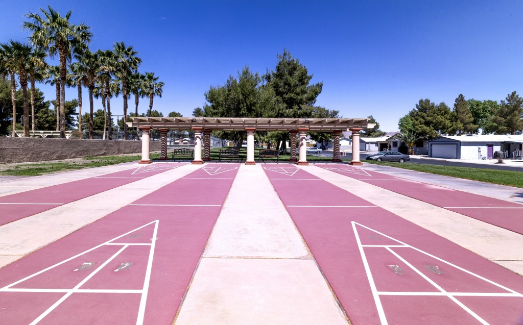 Four shuffleboard courts with covered seating.