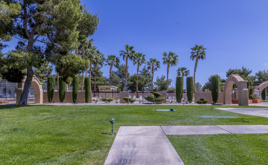 Lighted paved walkways amongst the trimmed green grass to the pool area. Large stone archways along the path. Tall trees and palm trees and trimmed shrubs.