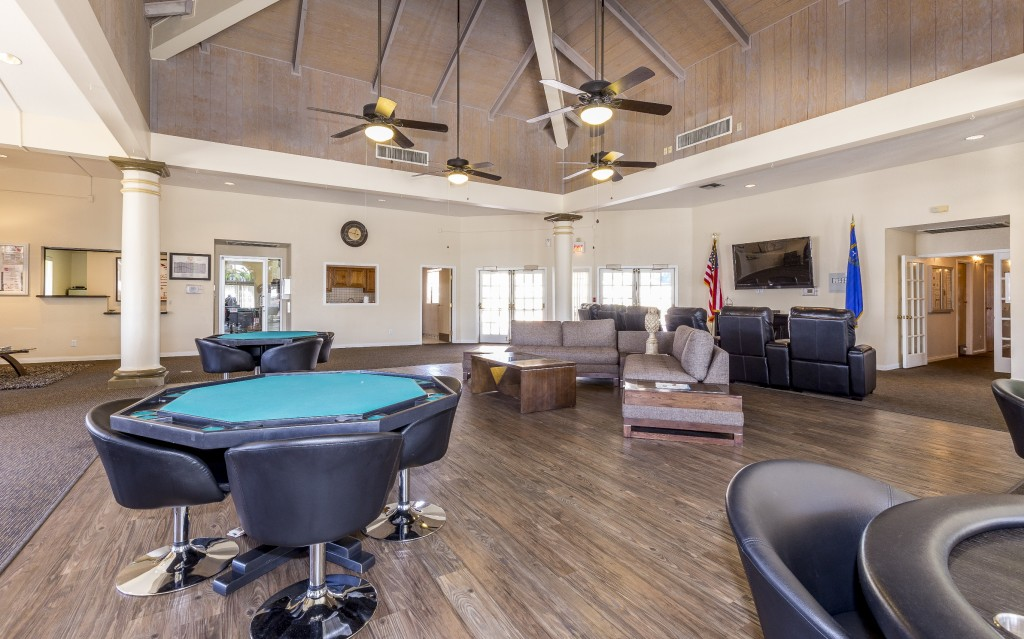 Large game area inside clubhouse with hardwood floors. Card tables with black leather chairs around them. Tall vaulted wood beamed ceilings and 4 ceiling fans. L shaped couch with 2 wood end tables and coffee table. Two decorative pillars on each side of game room. Black leather recliner chairs in front of flat screen TV mounted to wall.