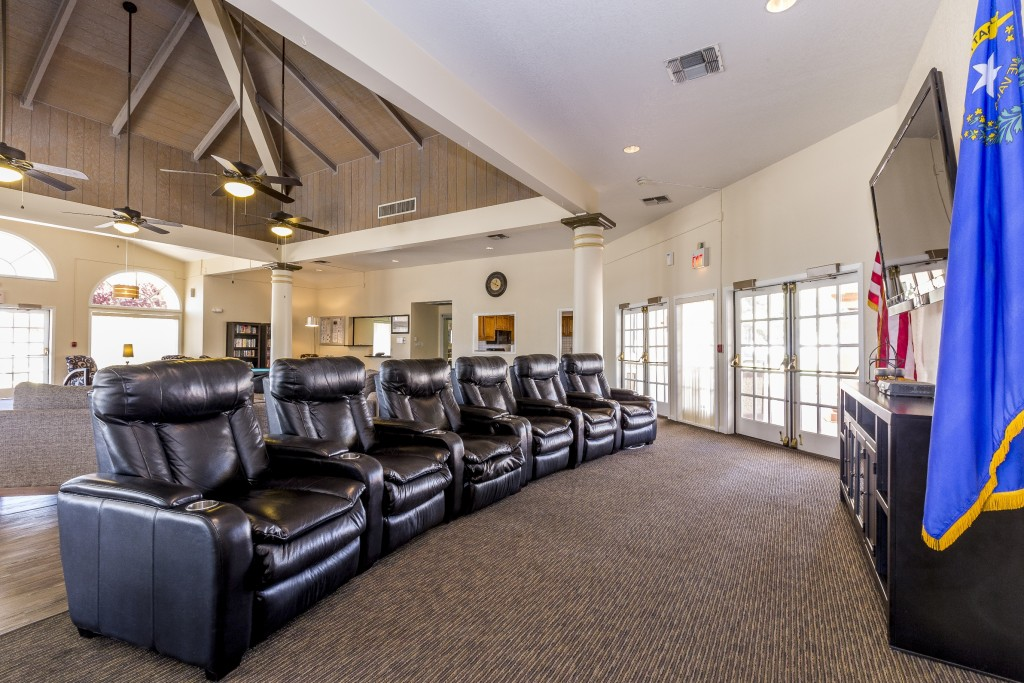 Clubhouse with tall vaulted ceilings. Comfy recliner chairs in lounge area with TV mounted on wall for viewing.