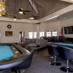 Large game area inside clubhouse with four card tables. Large vaulted ceilings with 4 fans hanging from above. Leather chairs around the card tables.