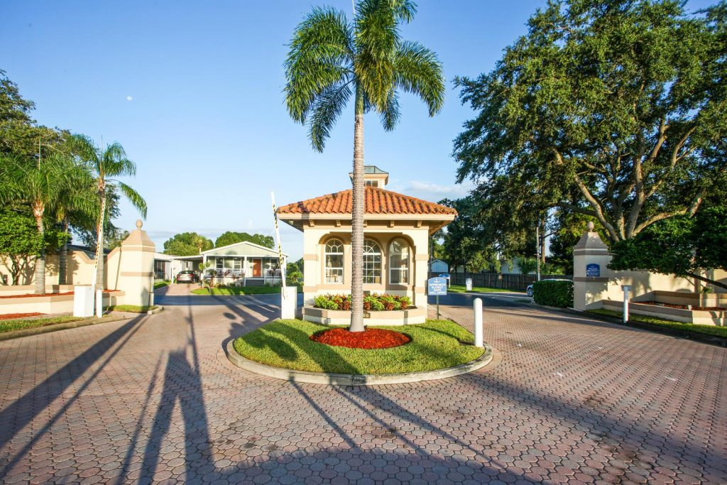 Gated entrance into Fountainview Estates, a 55 plus community. Security booth at entrance. Nicely landscaped with green grass, palm trees, full trees and brick pavers.