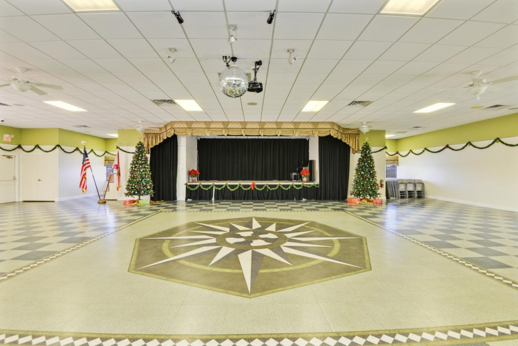 Large, spacious clubhouse that host many community wide events. A disco ball hands in the middle of the floor and 2 decorated Christmas trees sit at each side of the stage.