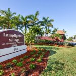 Beautifully landscaped front entrance to Lamplighter Village. Tall palm trees, green grass, and small plants surround the maroon and white stone sign indicating Lamplighter Village, an age qualified community.