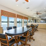 Enclosed meeting room as part of the clubhouse. Two conference tables with chairs overlook the lake with wide open windows. Tan cabinets