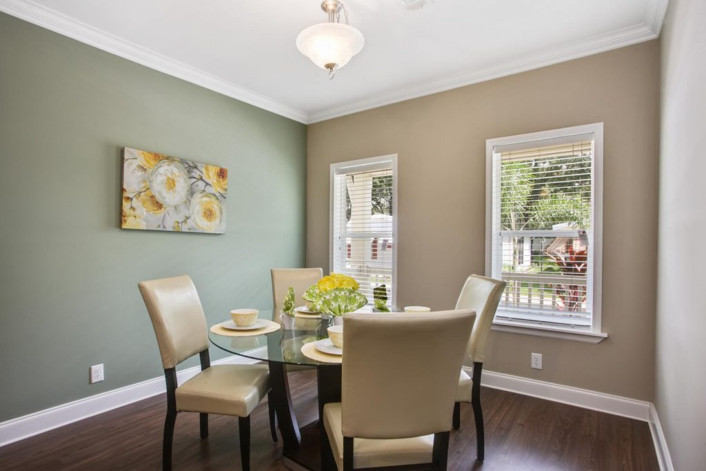 Spacious dining room that is bright and airy with 2 windows. hardwood floors with crown molding atop and bottom of walls. One wall is dark khaki in color and the other is sage green in color. Dining table is built of dark wood with circular glass top. Seating for 4 with cream, cushioned chairs