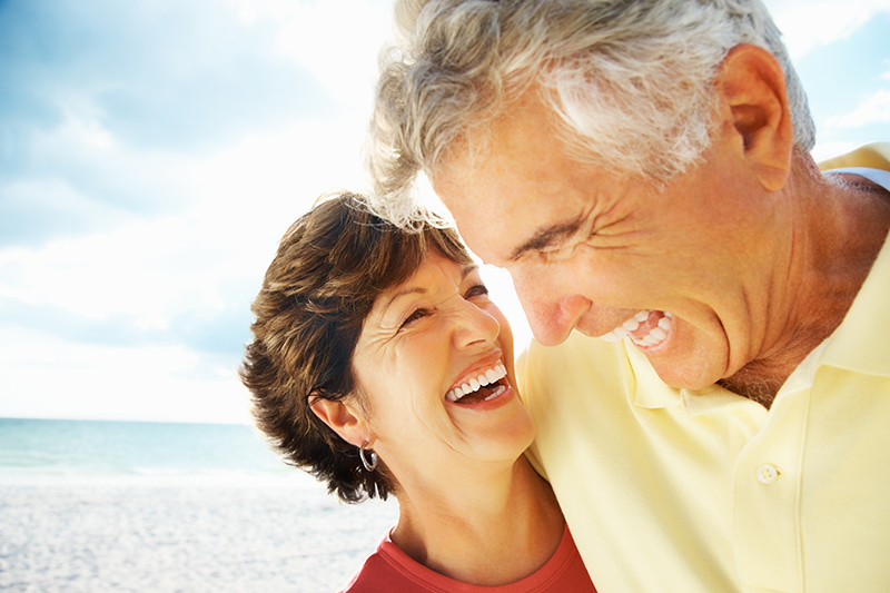 Portrait of a happy loving mature man and woman laughing on beach.