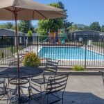 Outdoor fenced in swimming pool. Patio tables, chairs, and umbrellas.