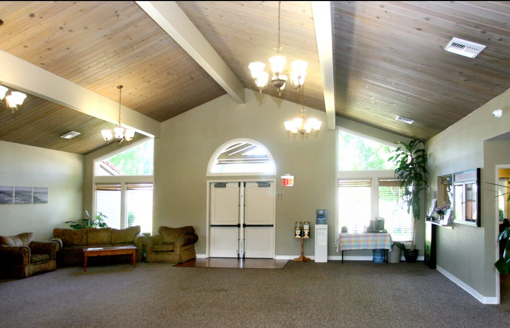 Carpeted clubhouse with vaulted ceiling. Loveseat and oversized chairs in corner.