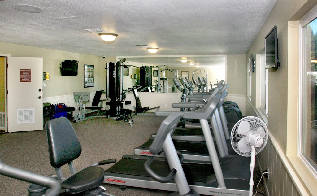 Fitness center with treadmills, weight machine, stationary bike and flat screen tvs mounted to wall.