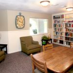 Book library with table and chairs. Clock on the wall. Bookcases built into wall with shelves of books.
