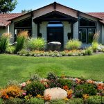 Outside clubhouse with green grass, shrubs and orange flowers.