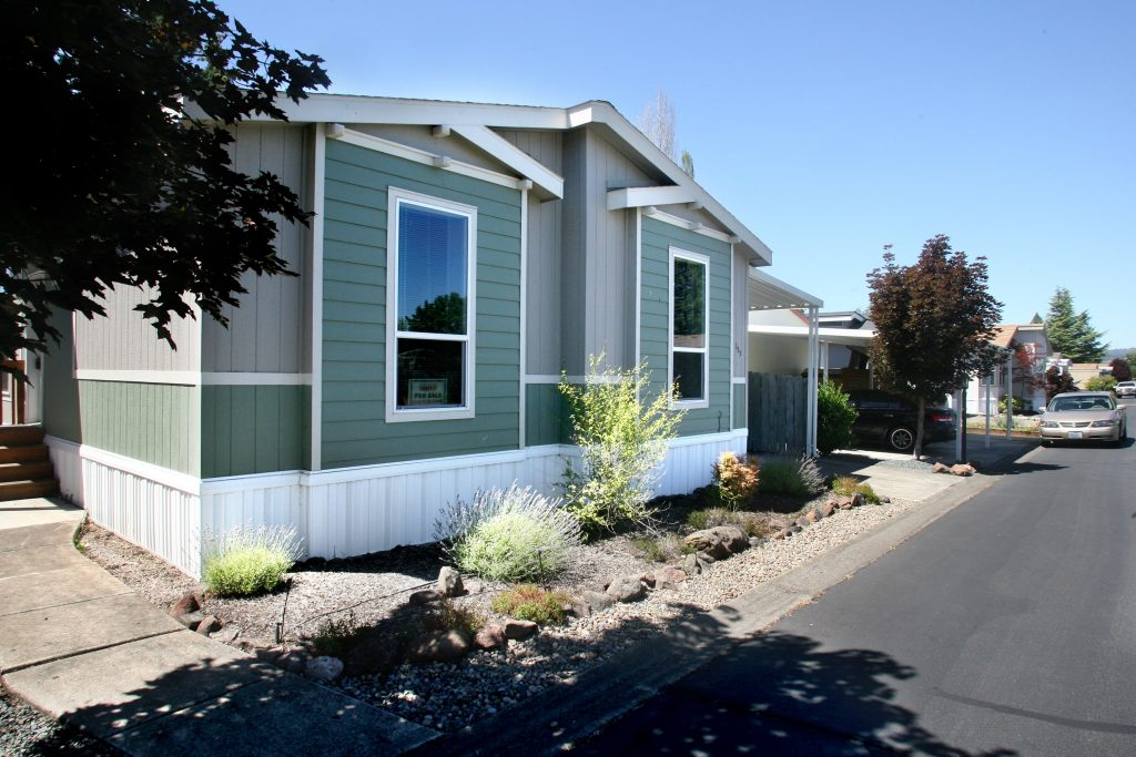 Clean paved neighborhood streets. Manufactured home green and gray trim.