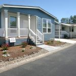 Homes for sale in Medford Estates, an all age manufactured home community. Home with blue-gray painted outside and white trim. Covered front porch with 3 white pillars. Few steps off porch. Landscaped with few white and red flowers.