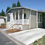 Manufactured home for sales. Gray with white trim exterior. Covered front porch. Covered carport and shed at end of driveway.