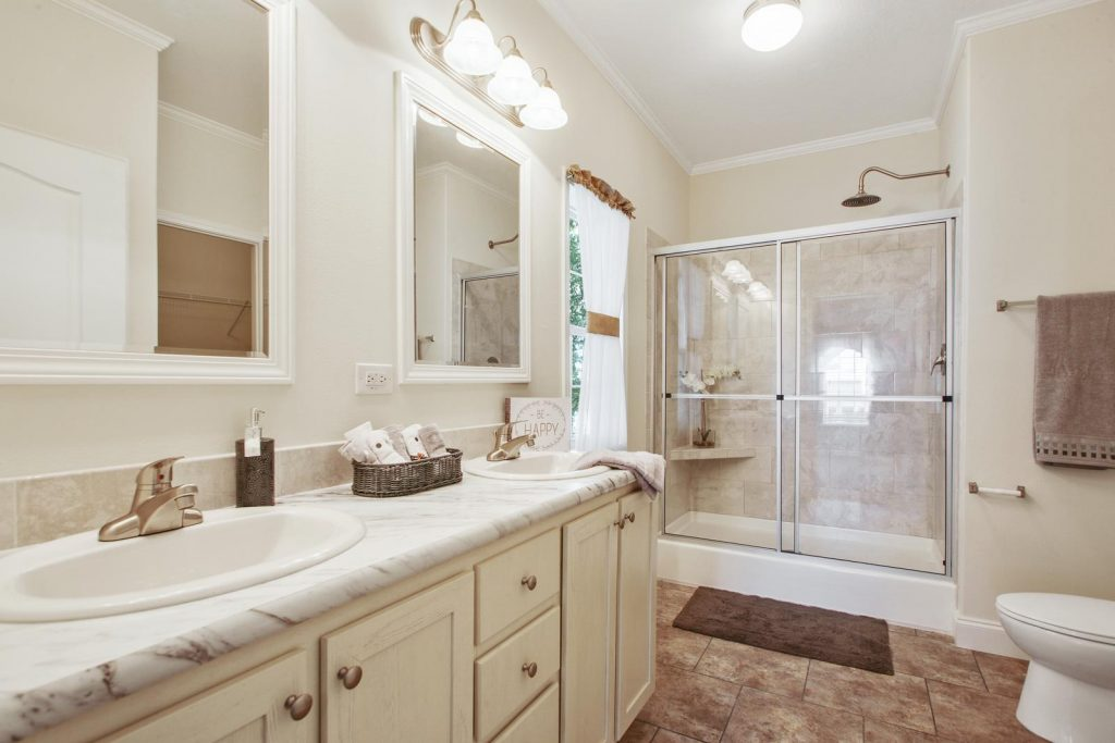 A modernized bathroom with his and her sinks. Tiled floor. Large step in shower with built-in shelf. Large showerhead. Towels are light brown with a brown shower rug.