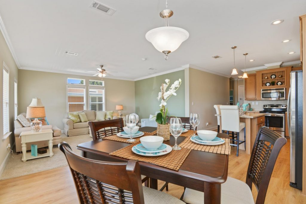 Spacious living area with dining room. Dark wood dining table with 4 wood cushioned chair. Place setting for four. Wood flooring throughout dining room and kitchen. Flows into living area and kitchen. Living room has tan carpet with light tan and sage green walls. Crown molding on top throughout. Tan loveseat sits in front of two windows