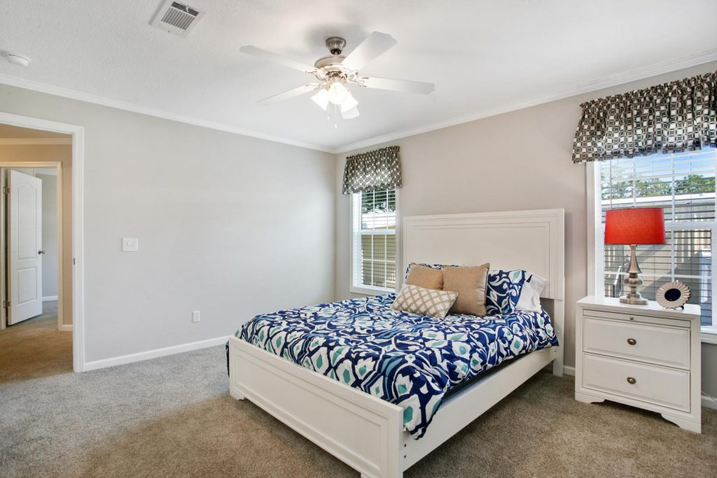 A bedroom with two windows and bed with white headboard and frame. Crown molding on top and bottom. A white nightstand with lamp and picture frame are next to bed. A blue, white, and teal comforter cover the bed with 3 bronze throw pillows. Carpet runs throughout.