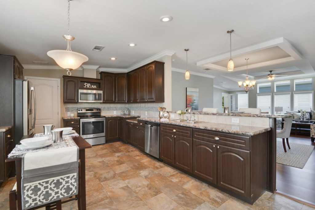 Beautiful new kitchen with dark wood cabinets and granite countertops. Stainless steel appliances. Recessed lighting and tile flooring. Opens up into living room.