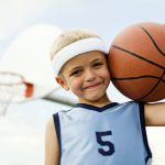 A young boy plays holds the basketball smiling.