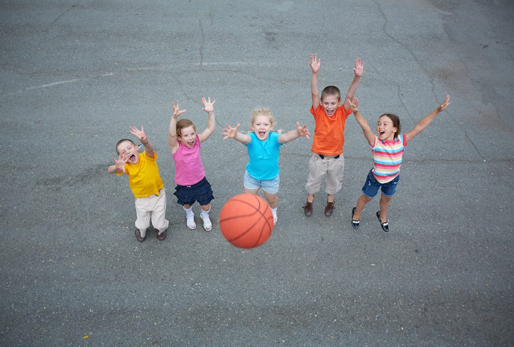 Five children playing basketball on the full-size basketball court.