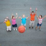 Five children playing basketball on the basketball court.