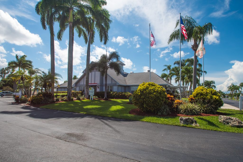 Clean, well paved roads lead up to the recreation center. Beautiful landscape with tall palm trees, green grass, trimmed shrubs. American flag flies high on a flag pole.