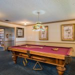 Billiards room with a pool table and mosaic lampshade with lighting hangs center from ceiling.
