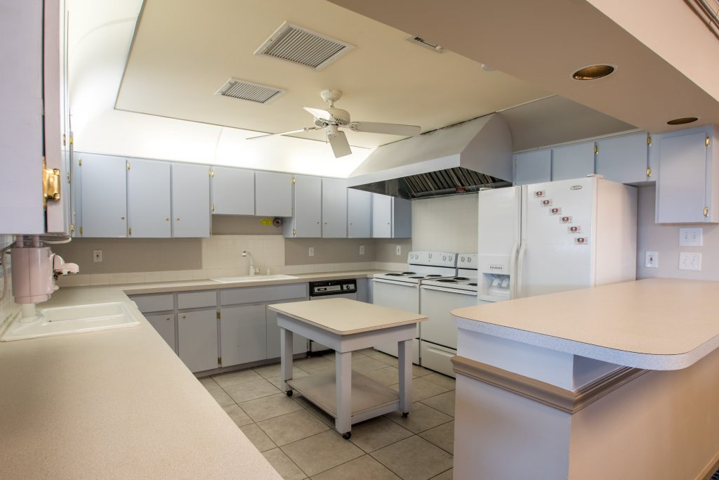 A commercial kitchen in the clubhouse with white cabinets and countertops. White fridge and two ovens, dishwasher and two sinks.