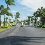 Palm Breezes Club is a gated community landscaped with palm trees down the clean wide paved street.