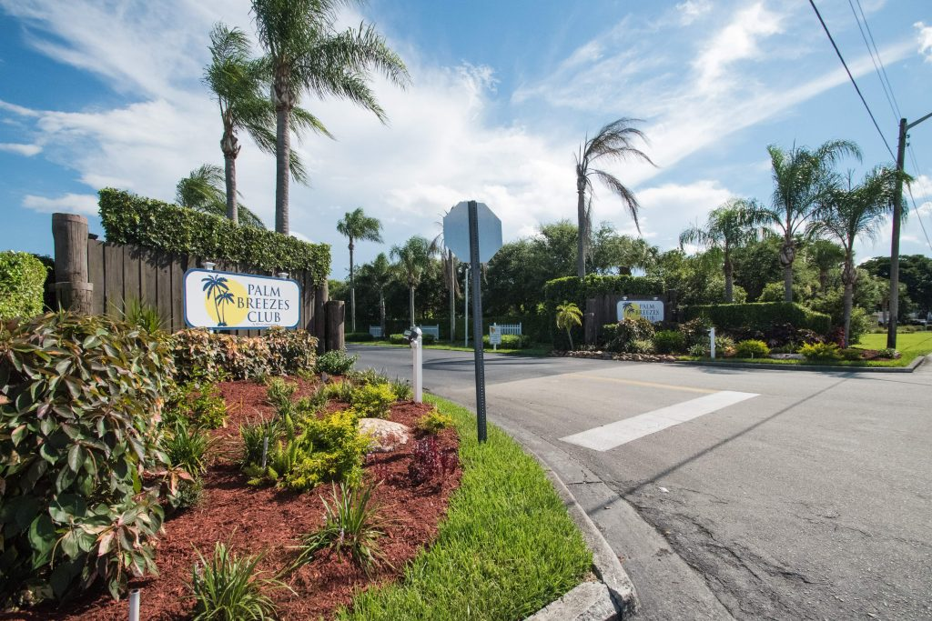 Palm Breezes Club has a well marked entrance with two signs on either side and flowing palm trees. Nicely landscaped with green grass and shrubbery.