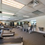 Fitness center in the community equipped with treadmills, weight machines and water fountain.