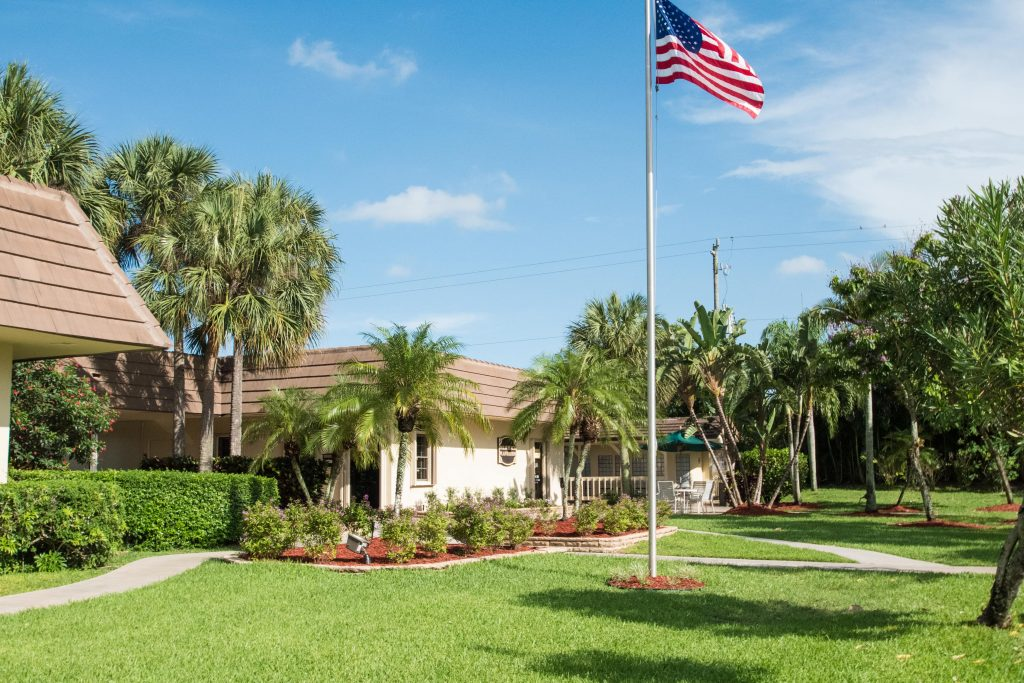 Beautiful landscape surrounds the Palm Beach Plantation. Green grass, palm trees, and lush, tall trees. Flagpole with American flag flying high in front of cluchouse.