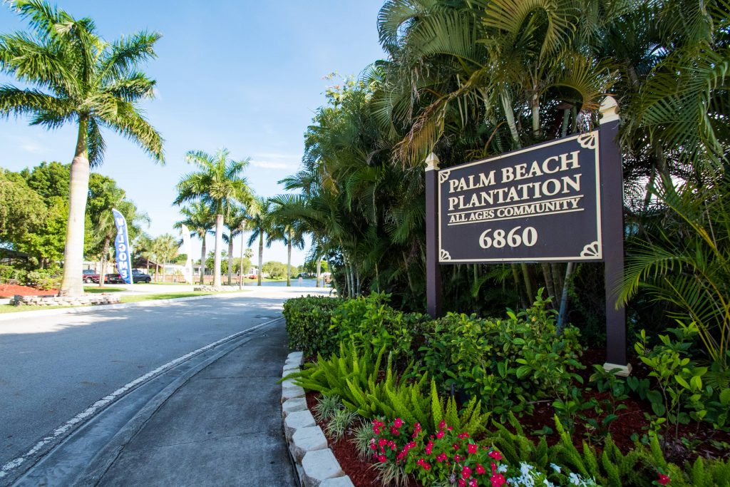 Palm Beach Plantation, an all ages community sign with colorful plants and lush shrubs around it. Palm trees grow behind the sign.