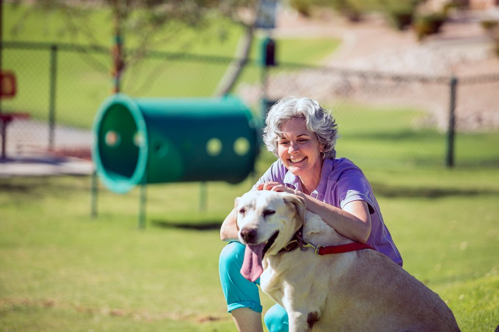 A 55 plus woman smiles big at the grassy dog park while kneeling and scratching the head of her large Labrador. Dog's tongue hangs out.