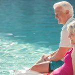 A retirement couple in their swimsuits smile while sitting along poolside with legs in the water
