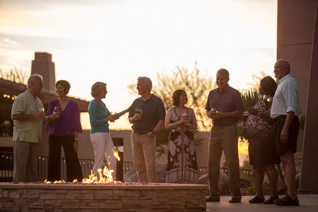 Montesa at Gold Canyon a 55+ community where couples are enjoying a cocktail around large fire pit at sunset