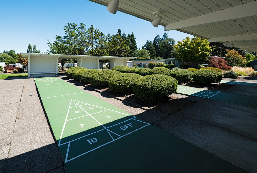 Shuffleboard courts with covered seating. Trimmed bushes inbetween each court. Tall full trees in the background.