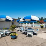 Royal Villas, a 55 plus manufactured home community with blue and white pool umbrellas. Tables and chairs. Potted plants around patio area.
