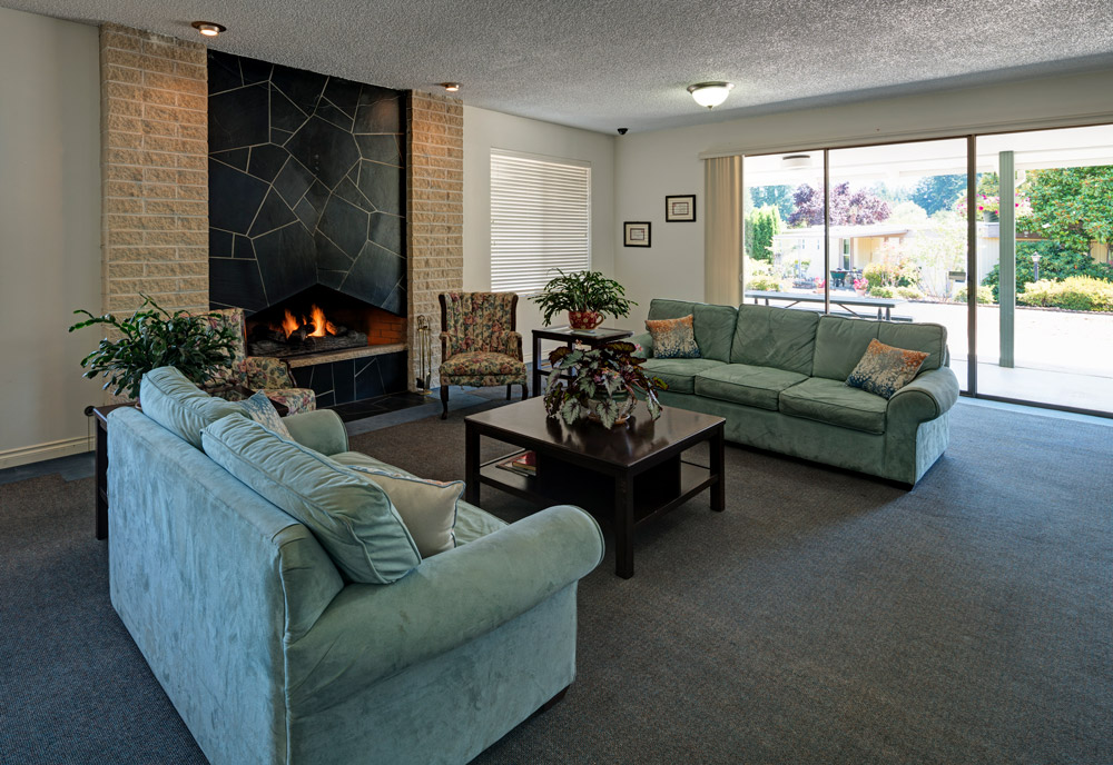 Lounge area inside community center with couch, loveseat, and coffee table. Two chairs sit on side of fireplace.
