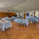 Ballroom set up with banquet tables and chairs. Vaulted ceiling with fans. White tablecloth.
