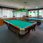 Billiards room with 2 pool tables. Large windows for natural light. Barstools and tables along the wall.
