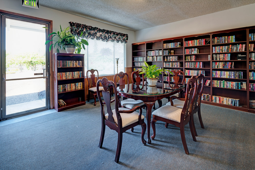 Library area with bookcases of books. Table and chairs for reading.