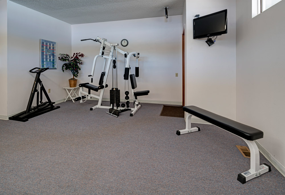 Fitness room with weight machine, bench and flat screen tv mounted to wall.