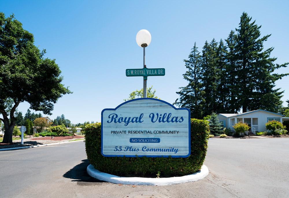 Royal Villas entrance sign into community. Beautiful tall, full trees in the background.