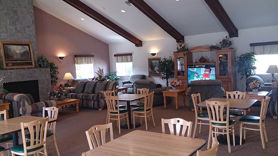 Inside clubhouse with tables and chairs. Entertainment center with tv. Couches around the stone fireplace. Vaulted ceiling.