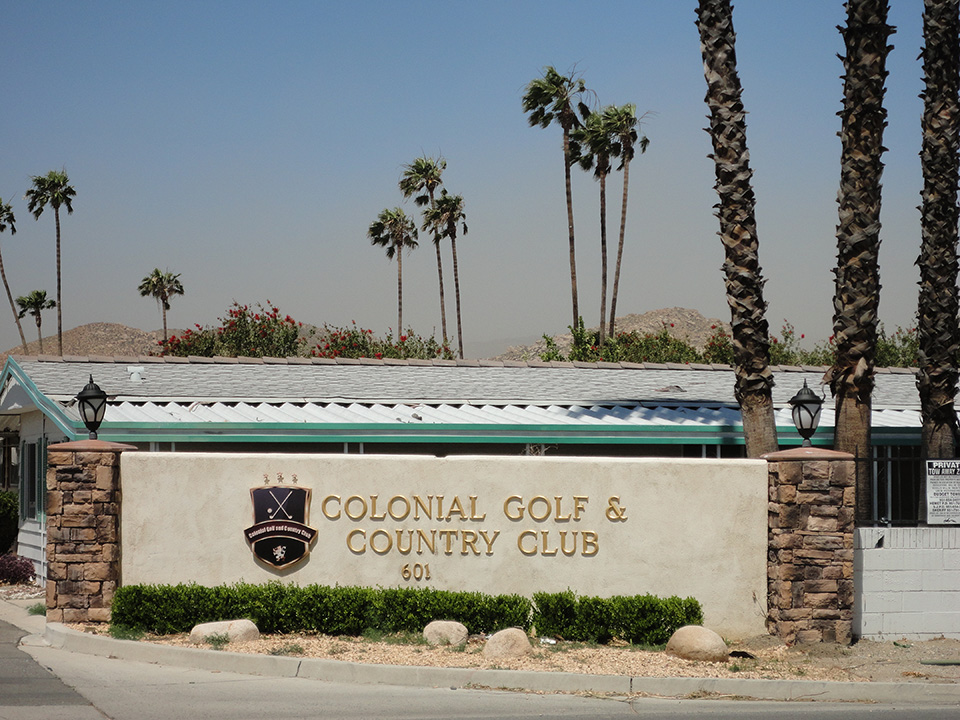 Entrance to the beautiful 55+community, golf course and country club. Greeted by a beige, cement wall labeled with Colonial Golf and Country Club, with light brick pillars on each side and palm trees in the background.