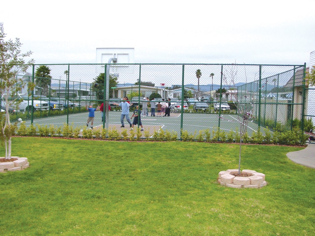Outdoor basketball court enclosed by gates for residents to enjoy shooting hoops or playing a game of basketball with friends and family.